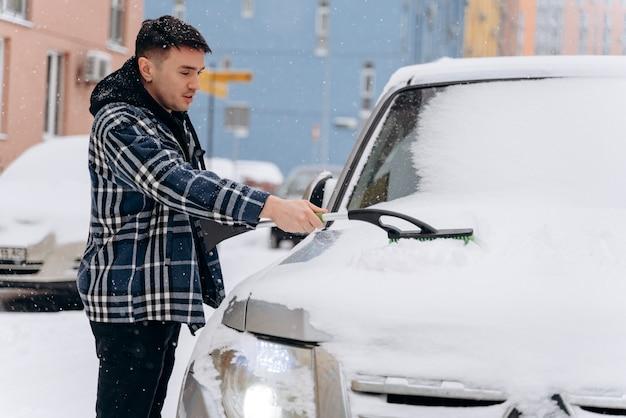 Aantrekkelijke man die sneeuw van zijn auto schoonmaakt tijdens de besneeuwde winterdag. transport-, voertuig- en autoverzorgingsconcept in de winter