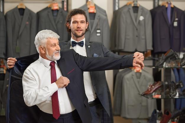 Aantrekkelijke man en oudere grijze man in kostuums in mannelijke winkel.