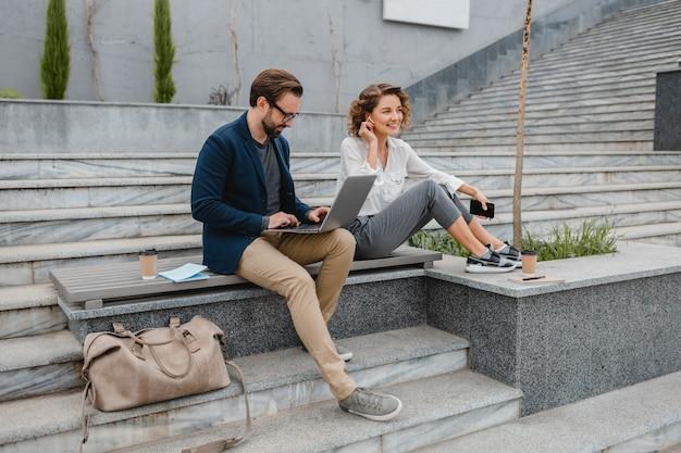 Aantrekkelijke man en vrouw zittend op trappen in het stadscentrum, pratend over handsfree draadloze oortelefoons