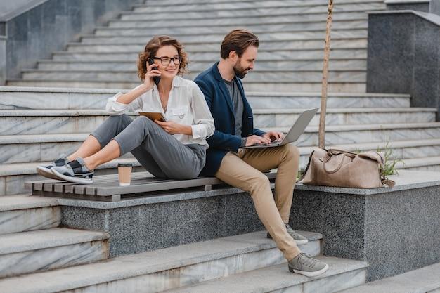 Aantrekkelijke man en vrouw zittend op trappen in het stadscentrum, werken samen op laptop