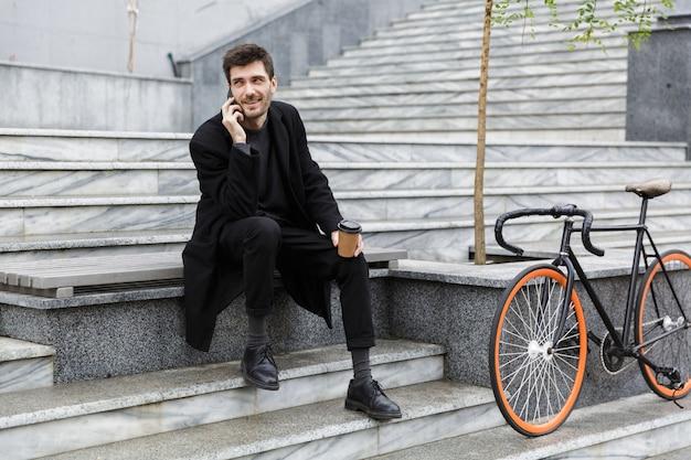 Aantrekkelijke man gekleed in jas zittend op de straat van de stad, praten op de mobiele telefoon, afhaalmaaltijden koffiekopje te houden