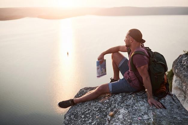 Aantrekkelijke man genieten van het uitzicht op het landschap van bergen boven de waterspiegel.
