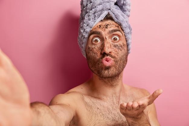 Aantrekkelijke man houdt de lippen gevouwen, stuurt luchtkus, maakt selfie-portret, past scrubmasker op gezicht toe, draagt handdoek op hoofd