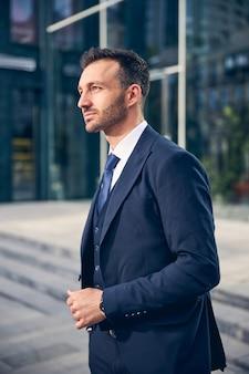 Aantrekkelijke man in blauw mooi pak die alleen op straat loopt en aan succes denkt