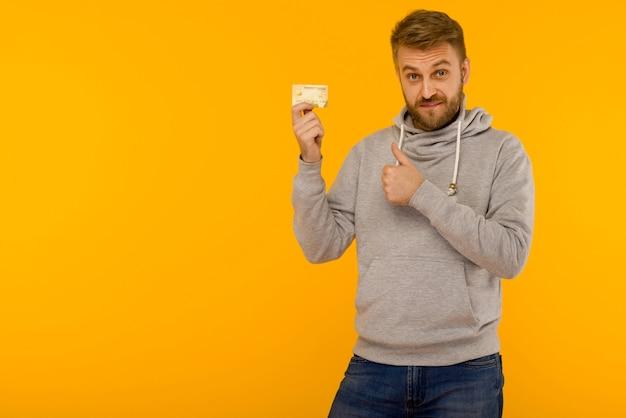 Aantrekkelijke man in een grijs sweatshirt stak een vinger omhoog en houdt een creditcard in zijn hand op een gele achtergrond