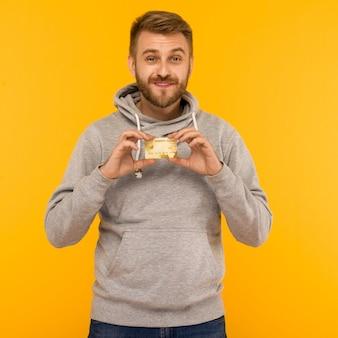 Aantrekkelijke man in een grijze hoodie heeft een creditcard in zijn handen op een gele achtergrond