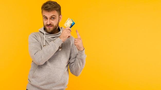 Aantrekkelijke man in een grijze hoodie wijst een vinger naar de creditcard