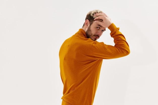 Aantrekkelijke man in een trui raakt zijn hoofd aan met zijn hand en een donkerblonde baard