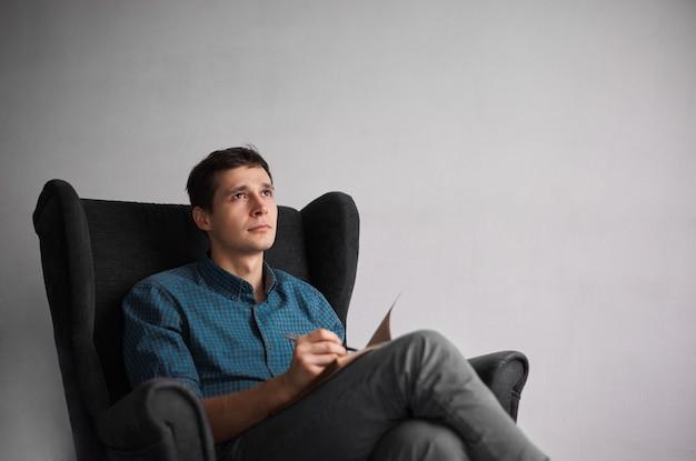 Aantrekkelijke man in geruite blauw shirt nieuwe ideeën schrijven in notitieblok met pen