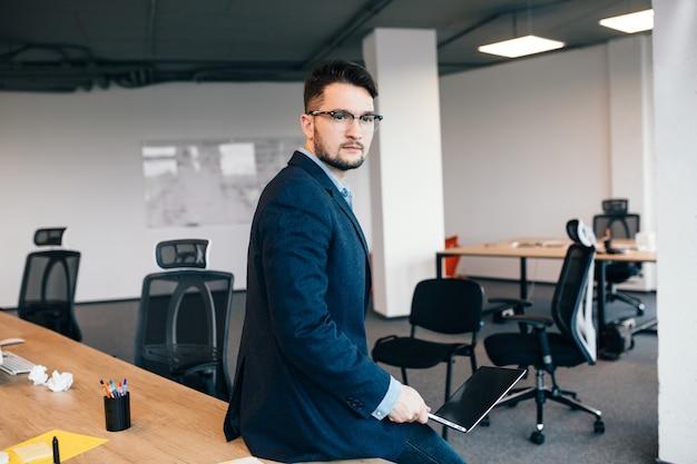 Aantrekkelijke man in glassess zit op tafel in de buurt van de werkplek op kantoor. hij draagt een blauw shirt, een donker jasje. hij ziet er serieus uit.