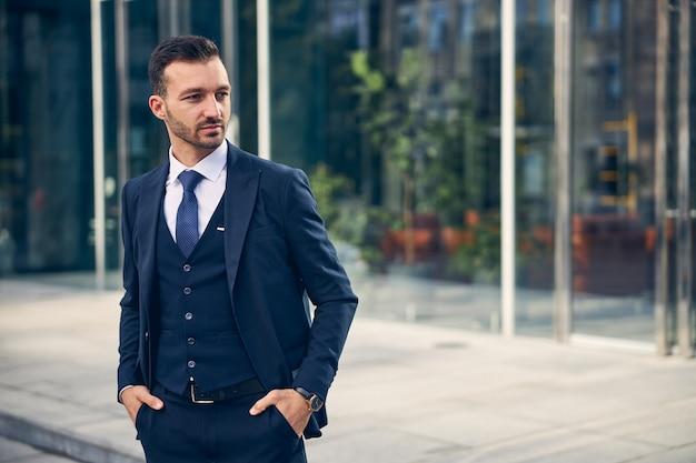 Aantrekkelijke man in jas, stropdas en broek die langs de straat loopt met de handen in de zakken
