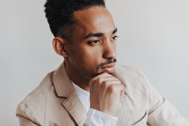 Aantrekkelijke man in lichte jas poseren op witte muur