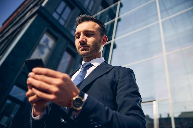 Aantrekkelijke man in pak en stropdas die buiten blijft terwijl hij iets checkt op zijn mobiel