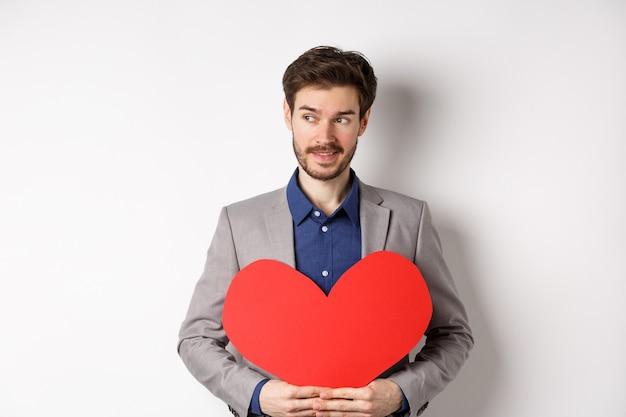 Aantrekkelijke man in pak op zoek naar links en glimlachend, met rood hart knipsel, valentijnsdag verrassing voor minnaar voorbereiden, staande op witte achtergrond.