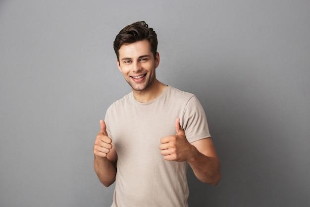 Aantrekkelijke man in t-shirt duimen opdagen met gelukkige glimlach