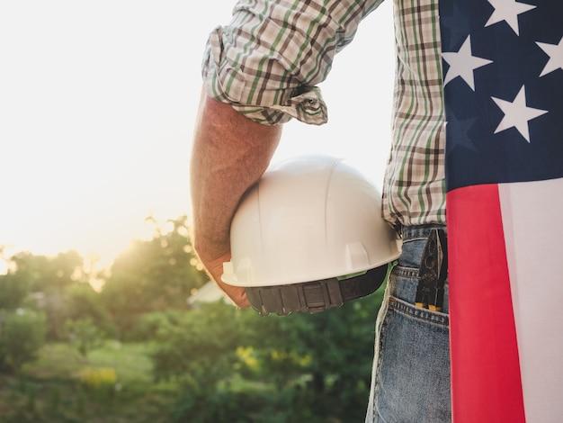 Aantrekkelijke man in werkkleding, met gereedschap in zijn handen tegen de achtergrond van bomen, blauwe lucht en zonsondergang. uitzicht vanaf de achterkant. arbeids- en werkgelegenheidsconcept
