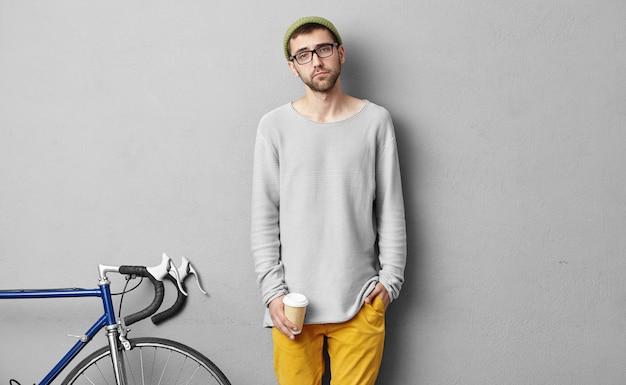 Aantrekkelijke man koffie te drinken na een wandeling op de fiets, staande in zijn kamer tegen grijze betonnen muur. vermoeide fietser die minuten na reis in hoge bergen rust heeft