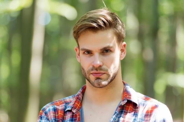 Aantrekkelijke man met bebaarde jonge gezichtshuid en stijlvol haar in casual stijl op zomerlandschap