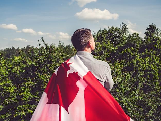 Aantrekkelijke man met canadese vlag. nationale feestdag