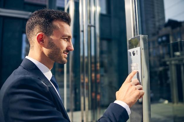 Aantrekkelijke man met designerbaard die buiten het zakencentrum blijft terwijl hij op de knop probeert te drukken