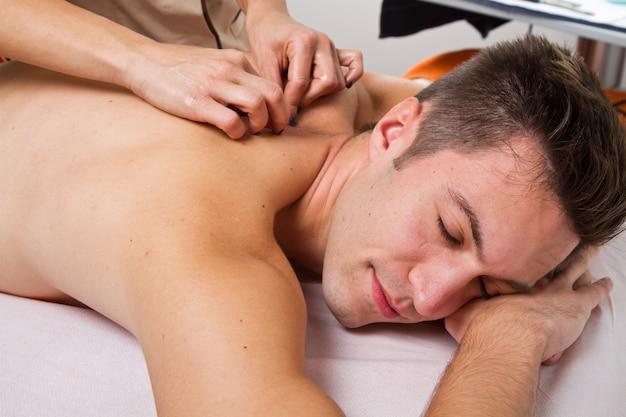 Aantrekkelijke man met een rugmassage in een schoonheidscentrum