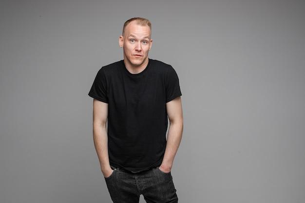 Aantrekkelijke man met kort blond haar, gekleed in een zwart t-shirt en spijkerbroek die de handen in de zakken houdt en verrassend iets