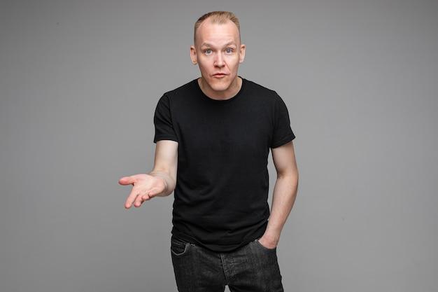 Aantrekkelijke man met kort blond haar, gekleed in een zwart t-shirt en spijkerbroek, kijkend naar de camera en wijst zijn hand naar copyspace