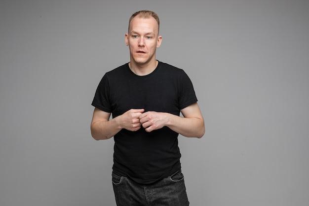 Aantrekkelijke man met kort blond haar in een zwart t-shirt en spijkerbroek houdt handen bij elkaar en praat