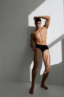 Aantrekkelijke man met naakt gespierd lichaam in zwart slipje