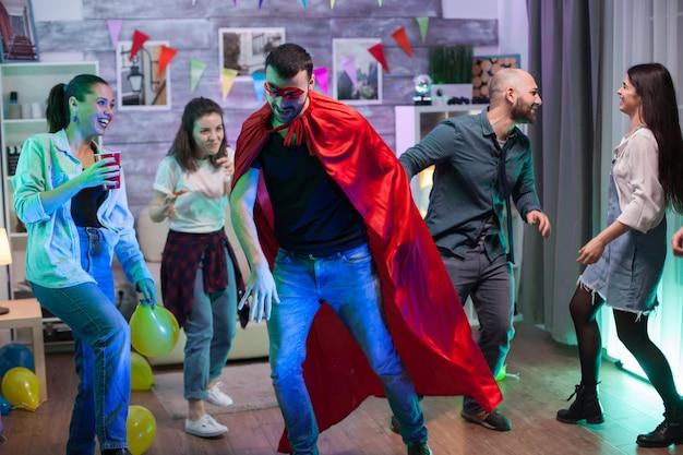Aantrekkelijke man met superheld kostuum en zijn vrienden dansen en drinken.