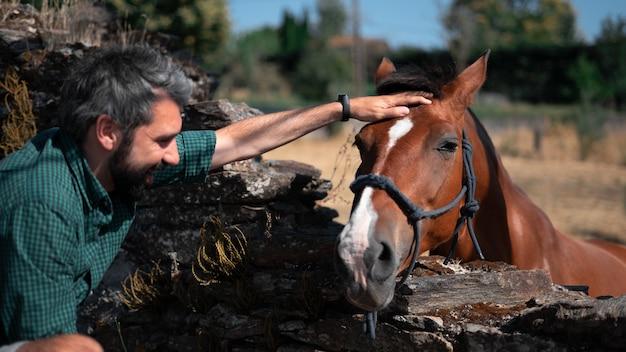 Aantrekkelijke man van middelbare leeftijd die het hoofd van een paard aait op een ranch
