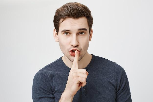 Aantrekkelijke man vraagt zwijg, zwijgend naar de camera