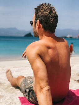 Aantrekkelijke man wegkijken zittend op het strand van blauw water