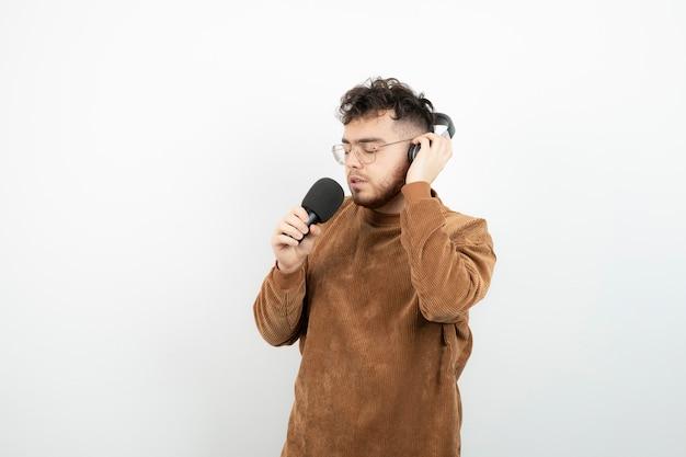 Aantrekkelijke man zingen een lied met microfoon over witte muur.