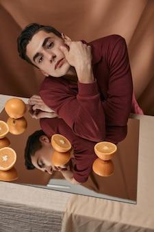 Aantrekkelijke man zit aan de tafel met sinaasappels op een spiegel close-up.