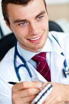 Aantrekkelijke mannelijke arts die een perscription schrijft