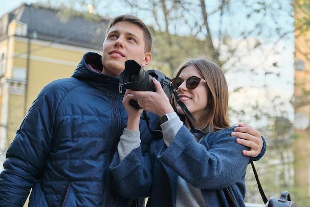 Aantrekkelijke mannelijke en vrouwelijke toeristen die foto's met fotocamera nemen