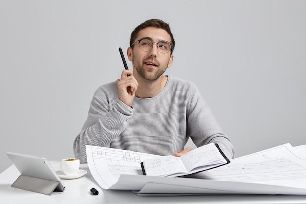 Aantrekkelijke mannelijke ingenieur of constructieve werknemer kijkt peinzend op, komt samen met gedachten