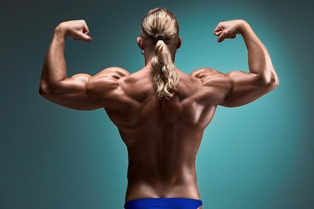 Aantrekkelijke mannelijke lichaamsbouwer op blauwe achtergrond