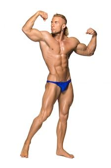 Aantrekkelijke mannelijke lichaamsbouwer op witte muur