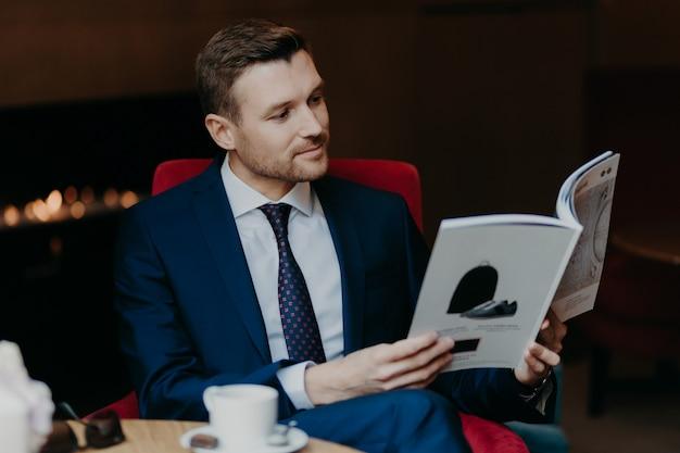 Aantrekkelijke mannelijke manager gekleed in zwart pak, wit overhemd en stropdas, leest tijdschrift in coffeeshop