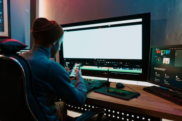 Aantrekkelijke mannelijke video-editor werkt met beeldmateriaal of video op zijn pc en heeft een pauze tijdens het communiceren op zijn smartphone. hij werkt in creative office studio of thuis. neon lichten