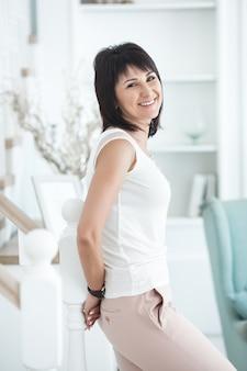 Aantrekkelijke medio volwassen vrouw binnenshuis. volwassen vrouwelijk portret. mooie vrouw thuis.
