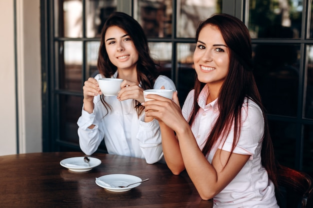 Aantrekkelijke meisjes die in koffie stellen, zoete koffie drinken. workflow