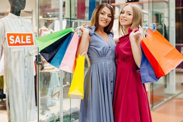 Aantrekkelijke meisjes met gekleurde tassen kochten veel dingen bij een uitverkoop