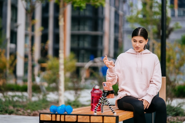 Aantrekkelijke meisjesblogger communiceert buitenshuis via smartphone