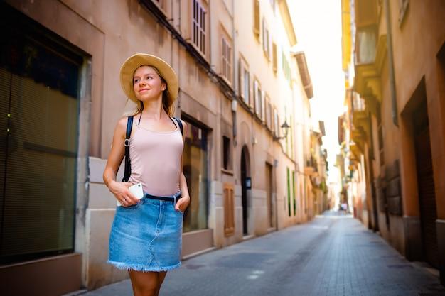 Aantrekkelijke meisjestoerist in hoed met rugzak die nieuwe stad in europa bij de zomer onderzoeken en haar telefoon met behulp van om foto te nemen