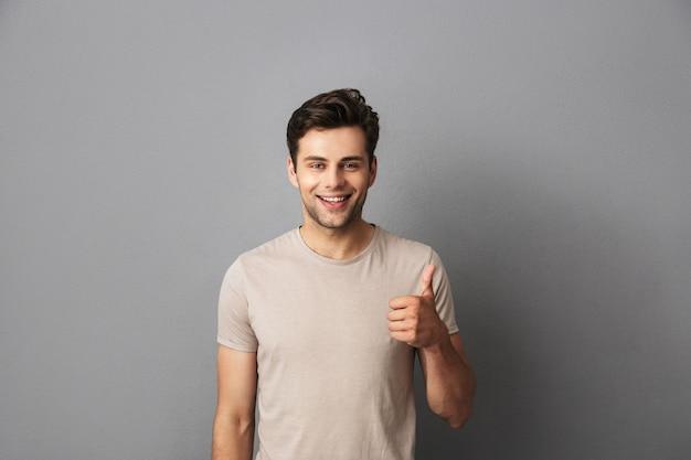 Aantrekkelijke mens die stoppelveld heeft dat duim met gelukkige glimlach toont