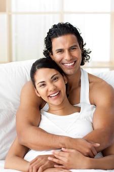 Aantrekkelijke mens die zijn vrouw koestert liggend op het bed