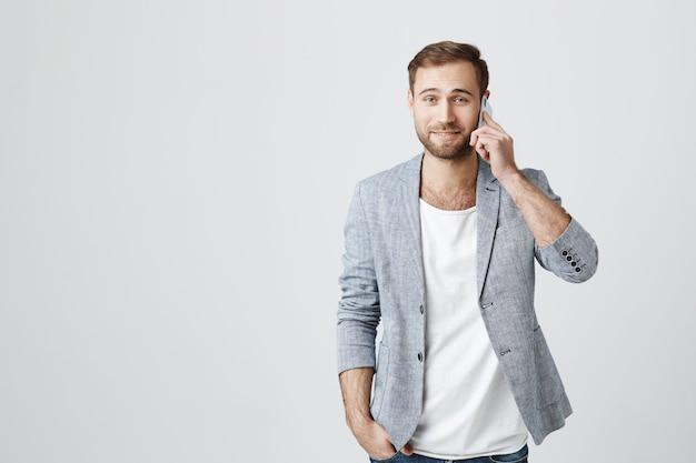 Aantrekkelijke mens in jasje dat telefoongesprek heeft